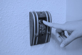 person about to pull a fire emergency lever